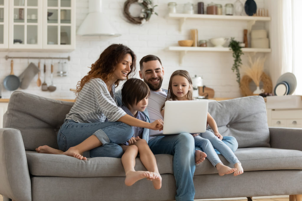 Happy family with kids sit on couch using laptop