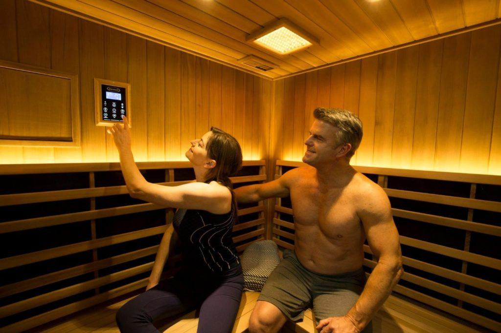 Man and woman adjusting temperature inside of a sauna